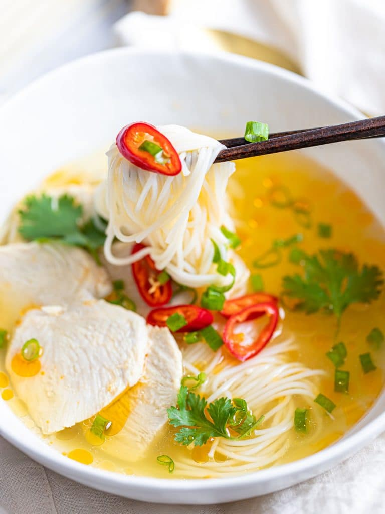 Asian chicken noodle soup with red peppers and herbs in a white bowl with chopsticks