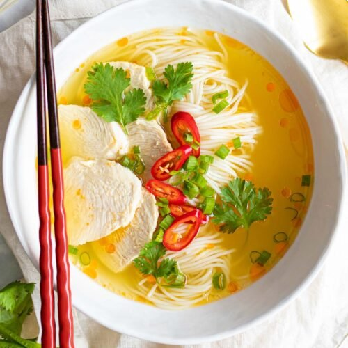 a bowl of easy Asian chicken noodle soup with red chopsticks, fresh herbs, red chilis, and chicken breast
