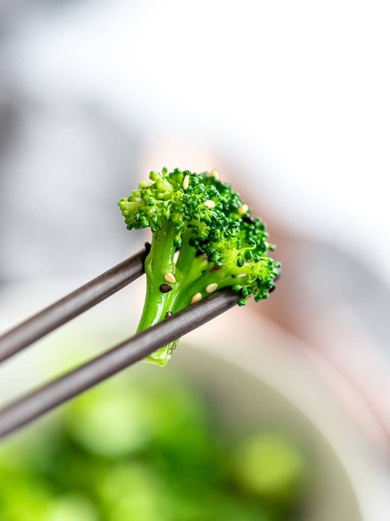 close up of Asian sesame broccoli salad held with chopsticks