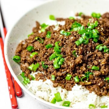 Korean beef bowl with rice and red chopsticks; bulgogi bowl