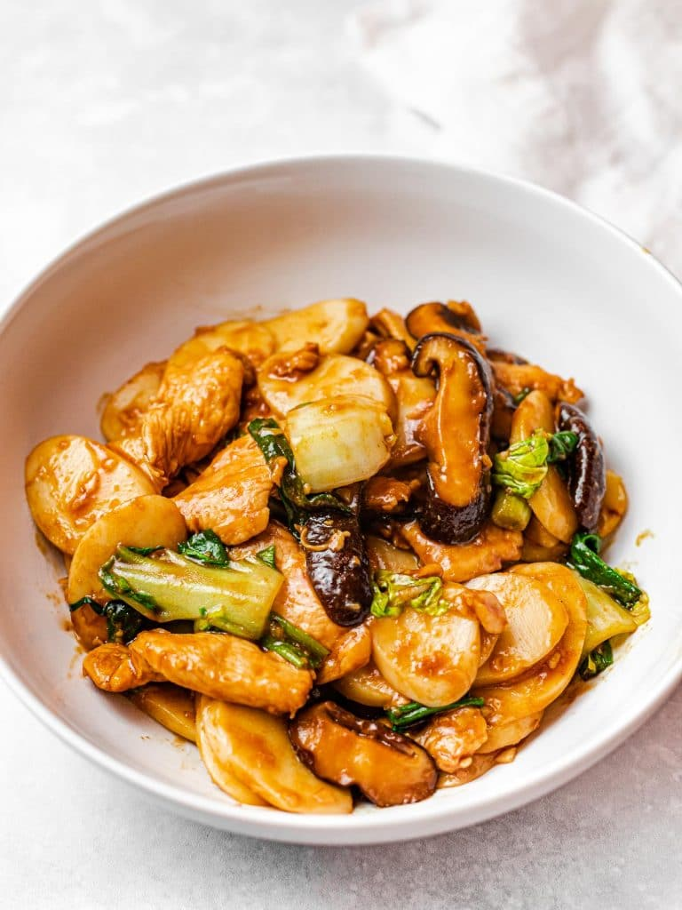Stir Fried Din Tai Fung Shanghai rice cakes, chao nian gao, with mushrooms and chicken in a white bowl