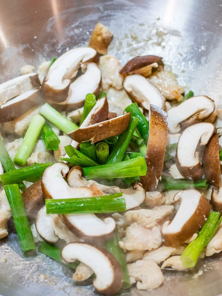 mushrooms, scallions, and chicken stir fried in a wok