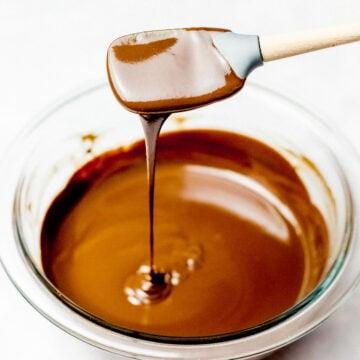 chocolate ganache dripping off a spatula into a glass bowl