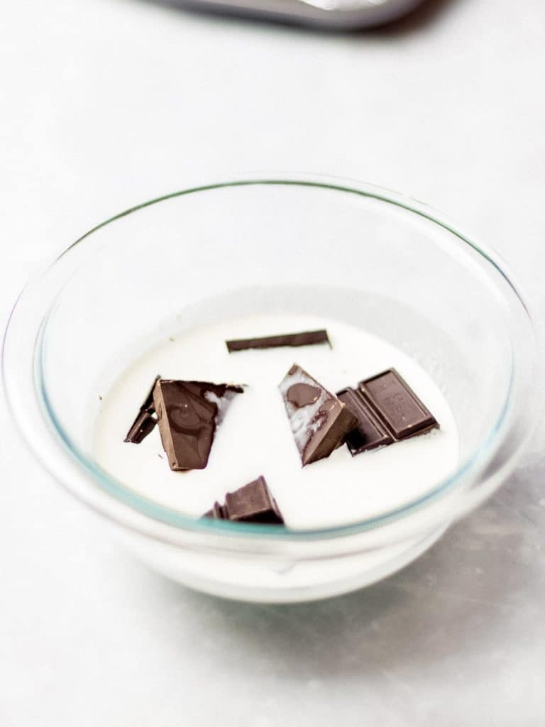 chocolate and heavy cream in a glass bowl