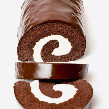 chocolate roll cake, swiss roll cake filled with cream and covered in a chocolate ganache glaze