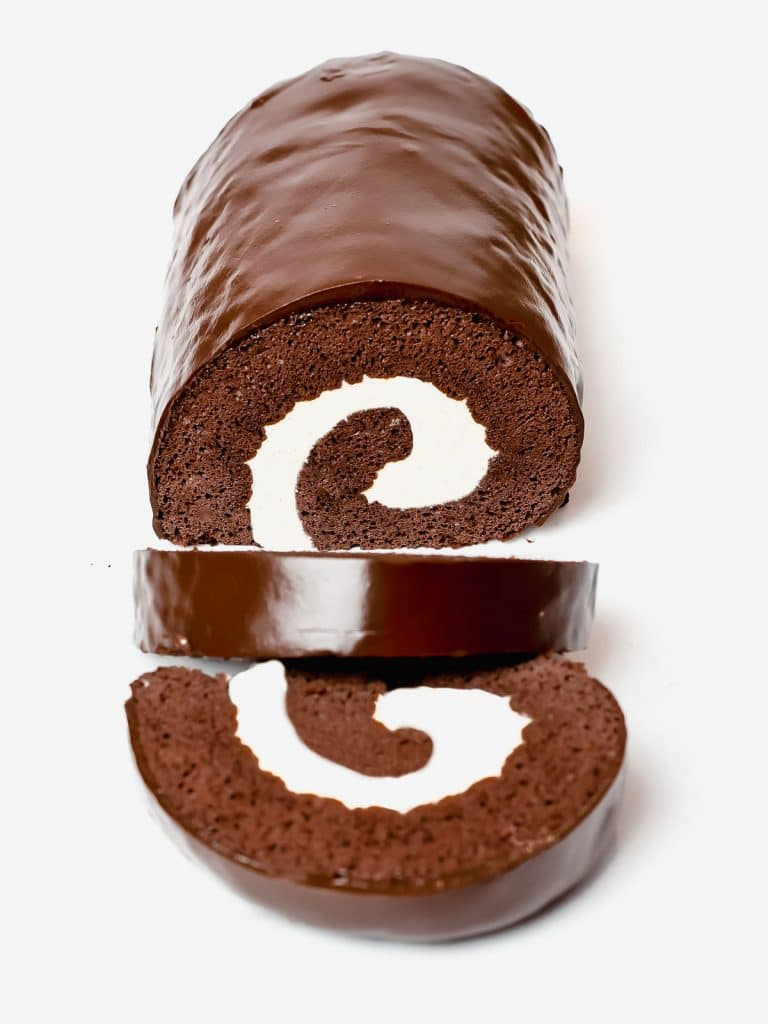 chocolate roll cake, known as swiss roll, filled with cream and covered with a chocolate ganache glaze