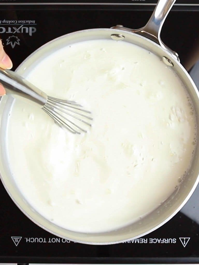 stirring milk with a whisk in a pot