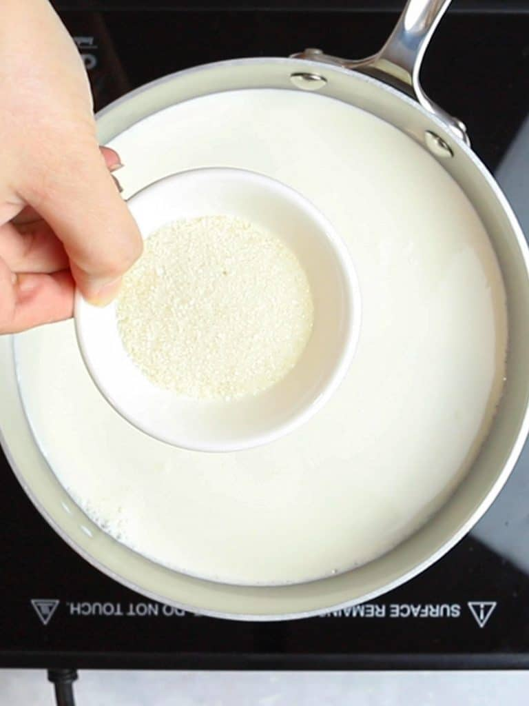 sugar in a small bowl with a pot of milk