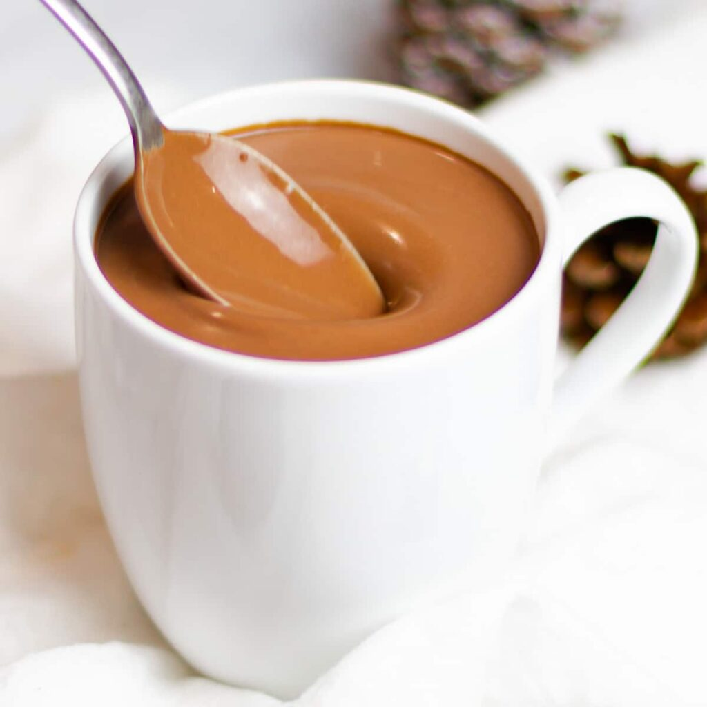 rich and creamy homemade hot chocolate in a white mug with a spoon