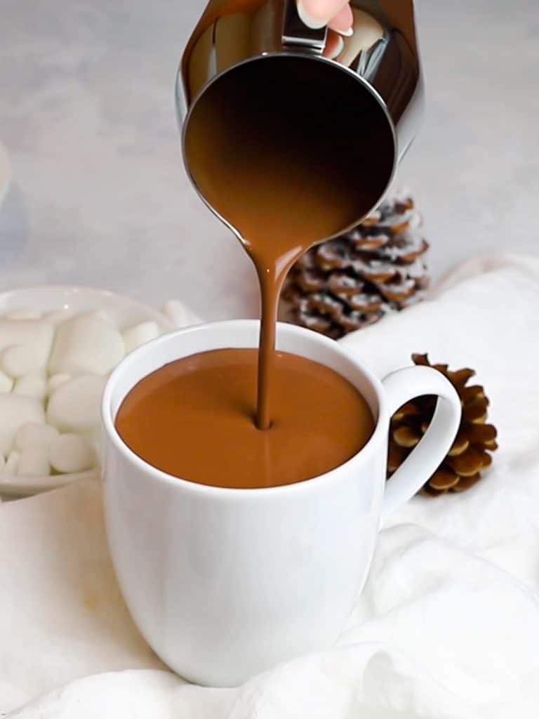 homemade hot chocolate being poured into a white mug