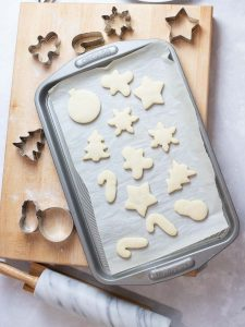 soft Christmas sugar cookies on a baking tray next to cookie cutters