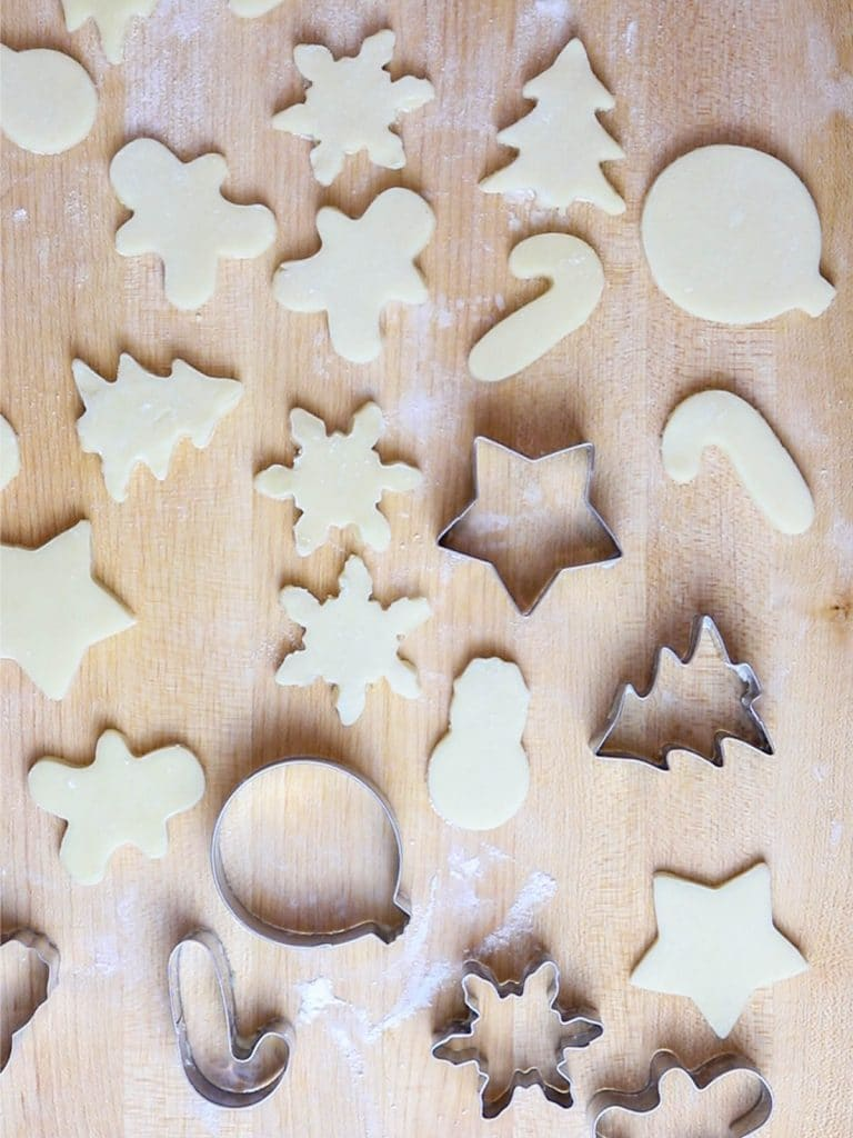 cut out Christmas sugar cookies on a wooden board