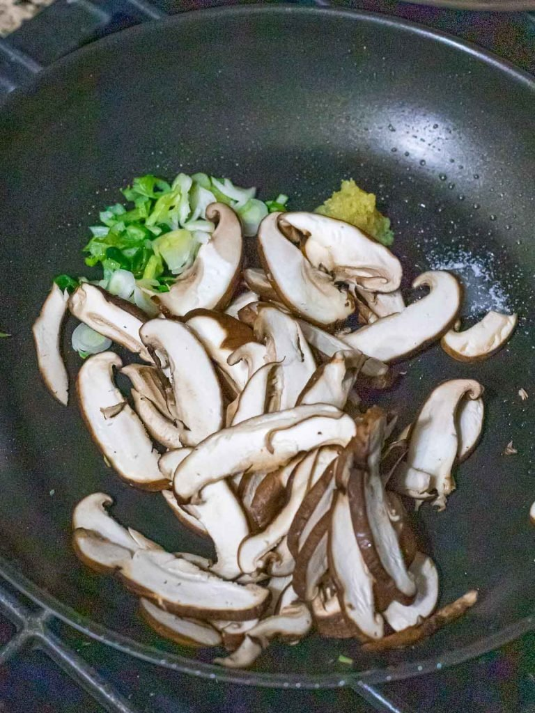 stir fried shiitake mushrooms in a dark pan