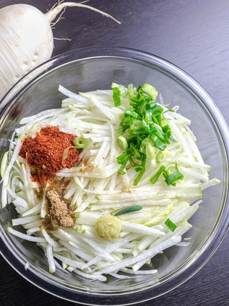 ingredients for daikon radish salad in a glass bowl