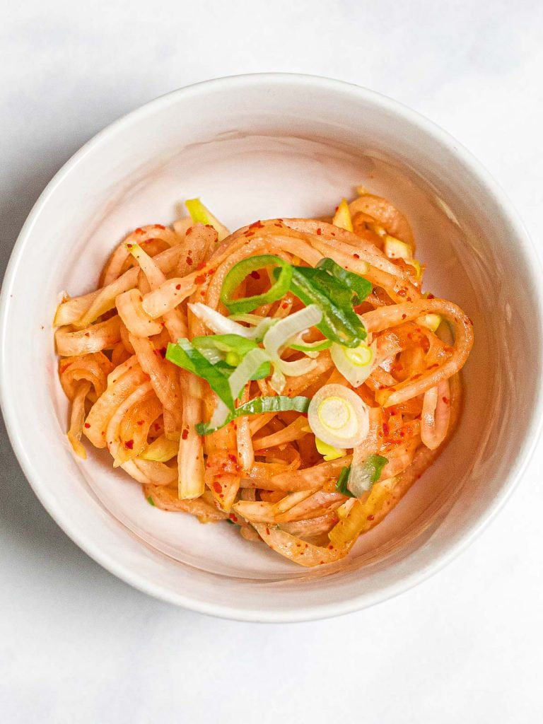spicy Korean radish salad in a small white bowl