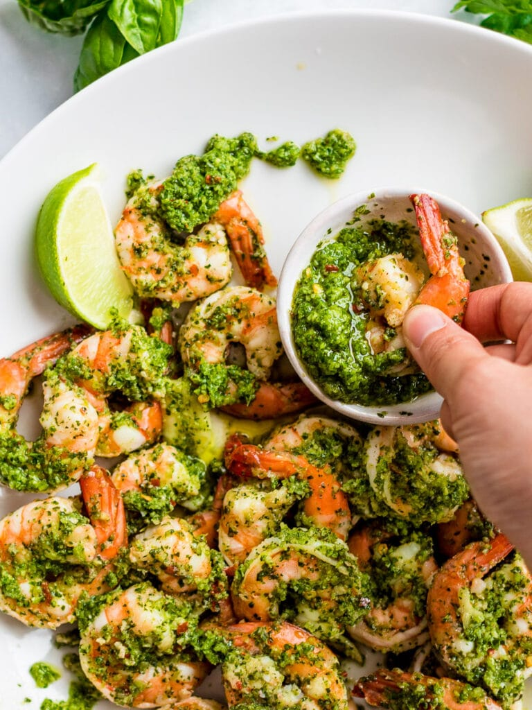 cilantro lime shrimp dipped in sauce on a white plate; copycat Costco cilantro lime shrimp