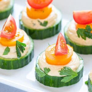 close up of cucumber hummus bites topped with red and yellow tomatoes