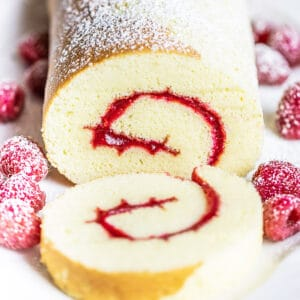 close up of Swiss jelly roll cake with raspberries and powdered sugar