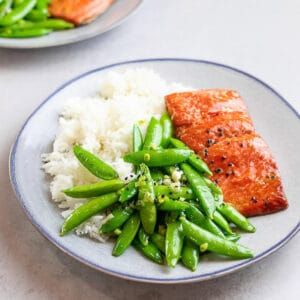 Teriyaki salmon and sugar snap peas with rice on a blue plate