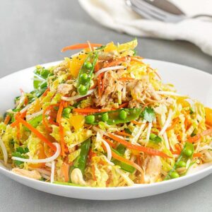 Chinese chicken salad with peas and carrots on a white plate