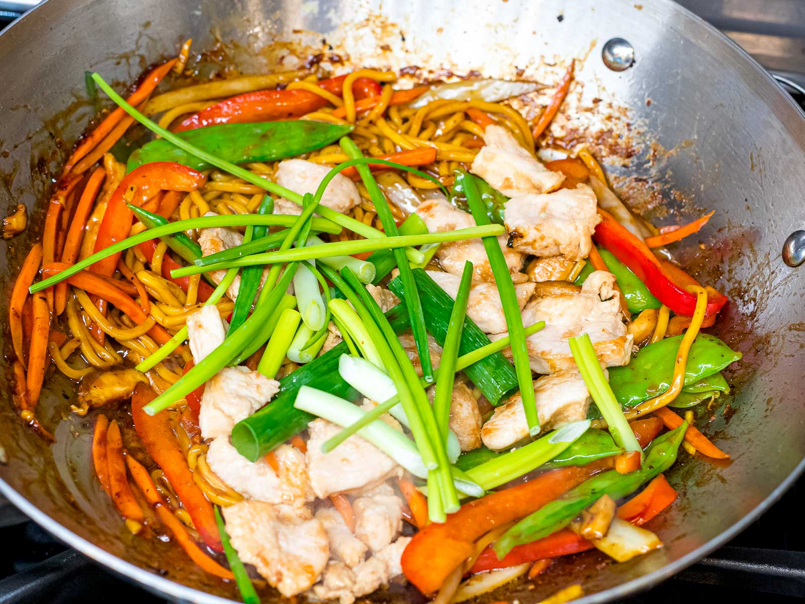lo mein noodles, chicken, and chinese chives with vegetables in a wok
