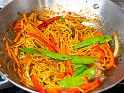 lo mein noodles with snow peas, red peppers, and carrots cooking in a wok