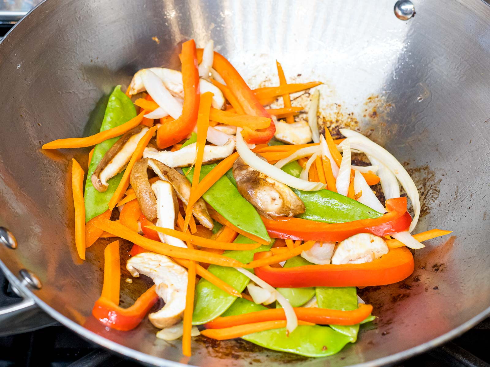 snow peas, carrots, red bell peppers, and shiitake mushrooms in a wok