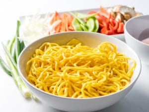 fresh Chinese egg noodles next to vegetables in a white bowl
