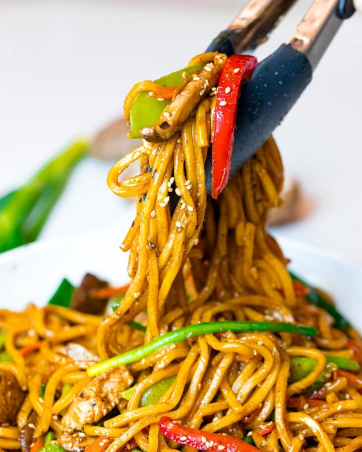 easy chicken lo mein with vegetables held by tongs