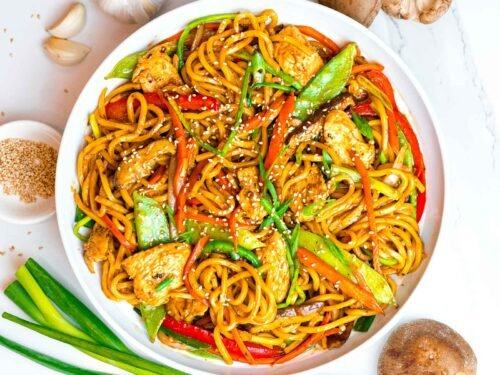 easy chicken lo mein with vegetables in a white bowl