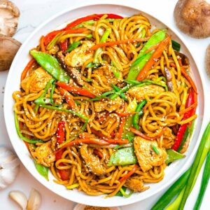 easy chicken lo mein noodles with vegetables next to scallions and mushrooms