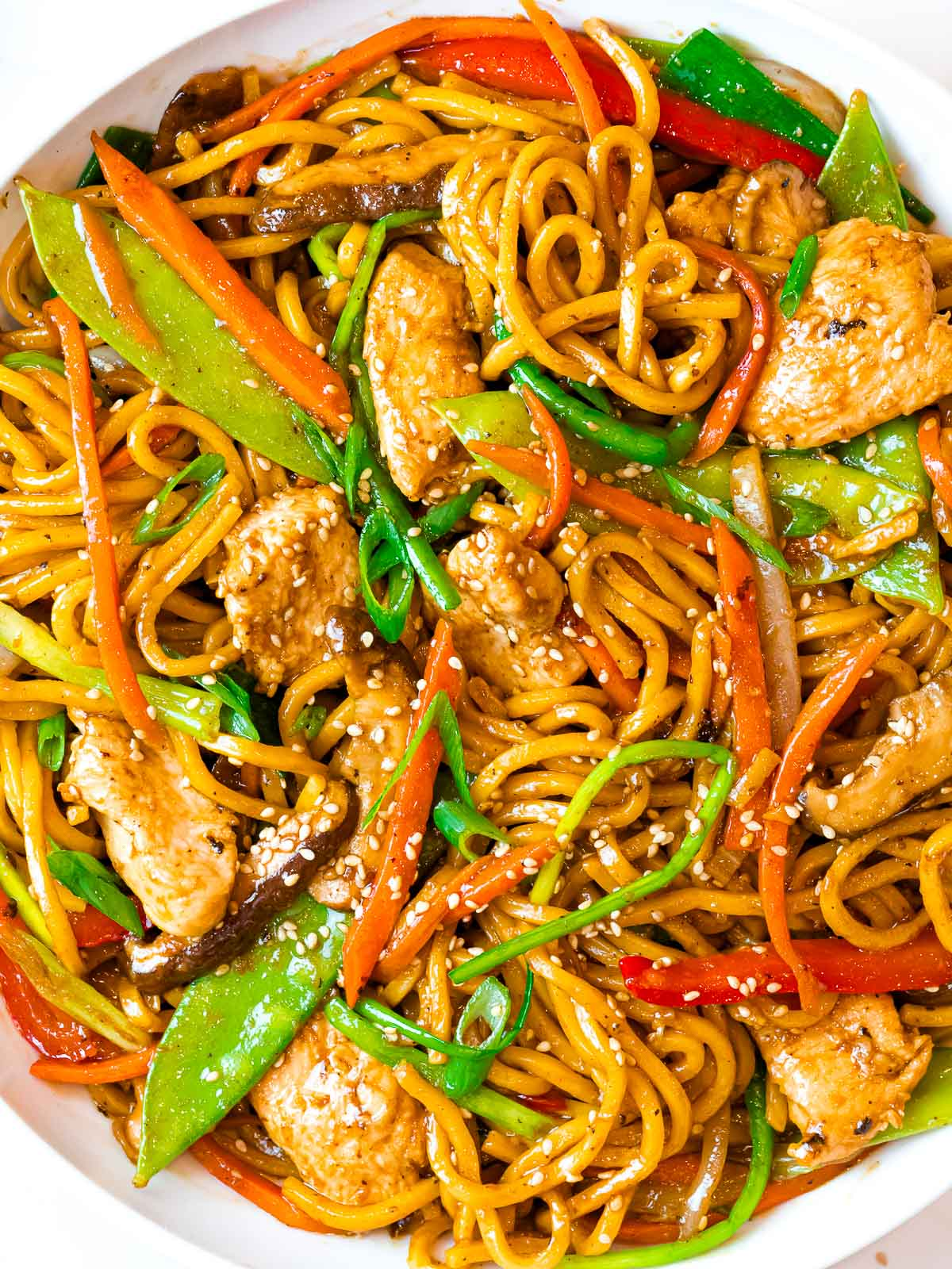 close up of restaurant style chicken lo mein in a bowl with vegetables