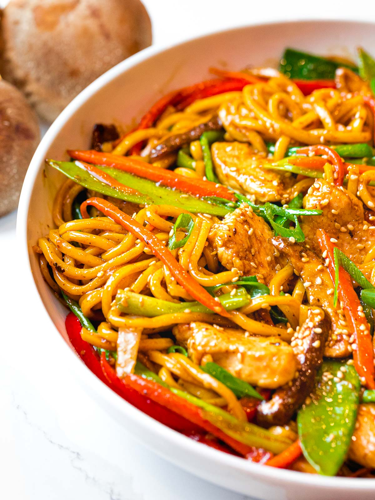 close up of restaurant style chicken lo mein with vegetables in a white bowl