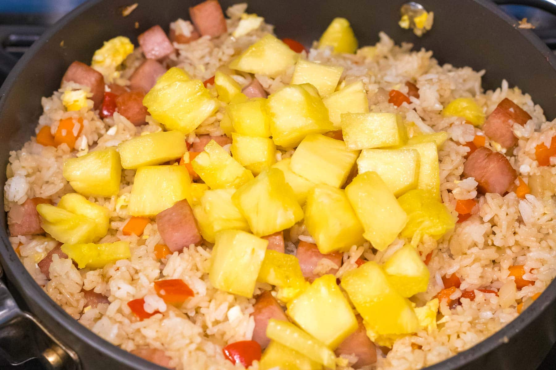 fried rice with spam and pineapple chunks in a pan