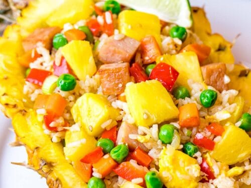 pineapple fried rice with pineapple chunks, ham, and peas served in a pineapple boat