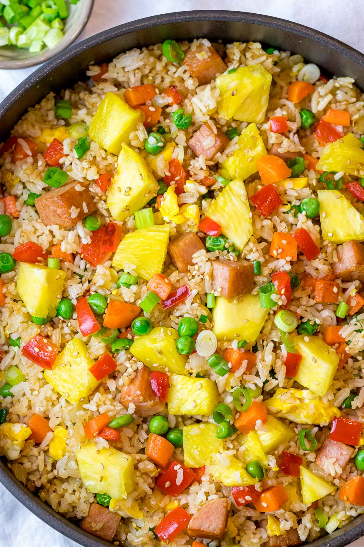 Hawaiian pineapple fried rice with fresh pineapples, spam, peas, and carrots in a pan