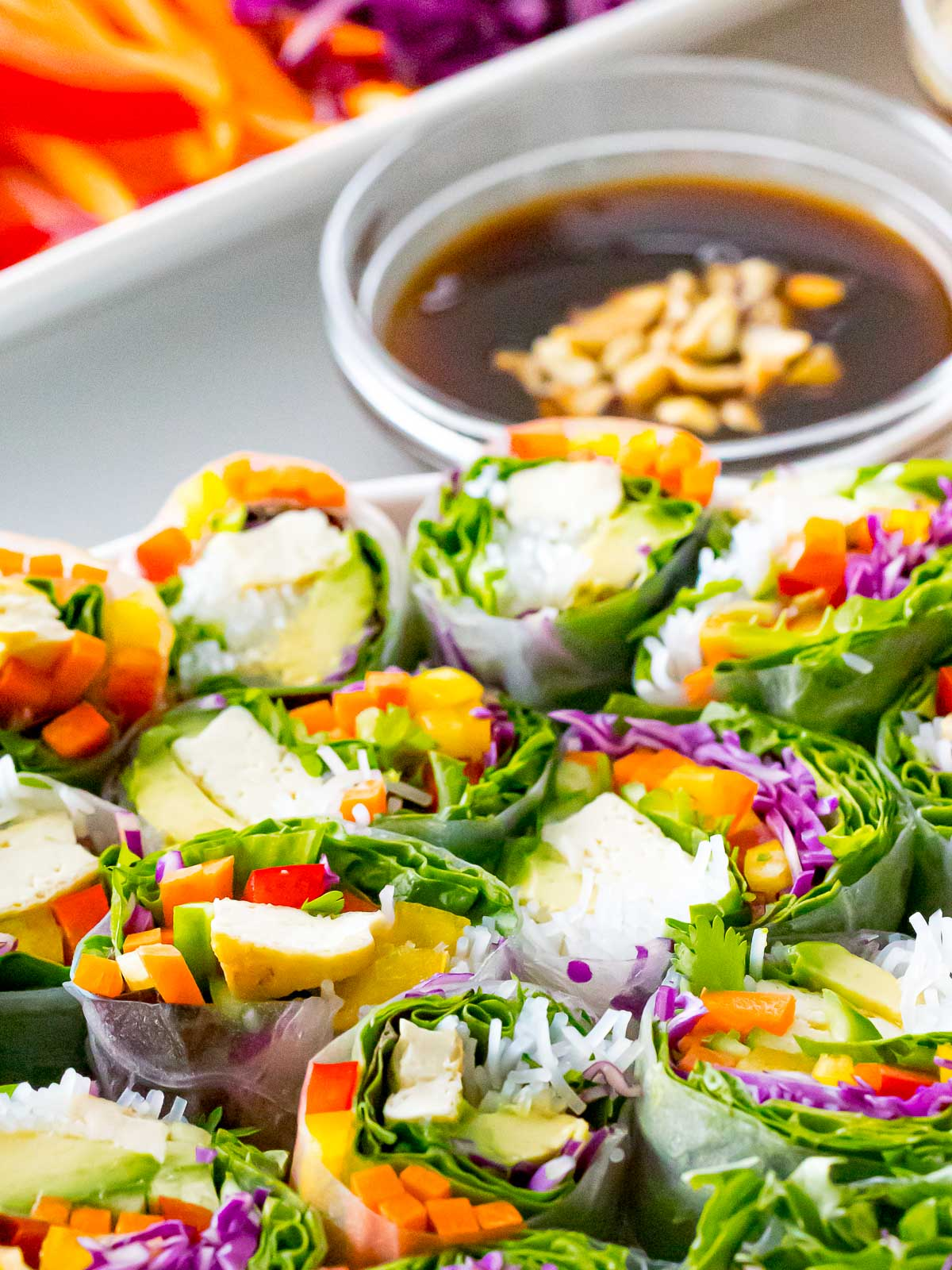 hoisin dipping sauce next to a plate of fresh spring rolls