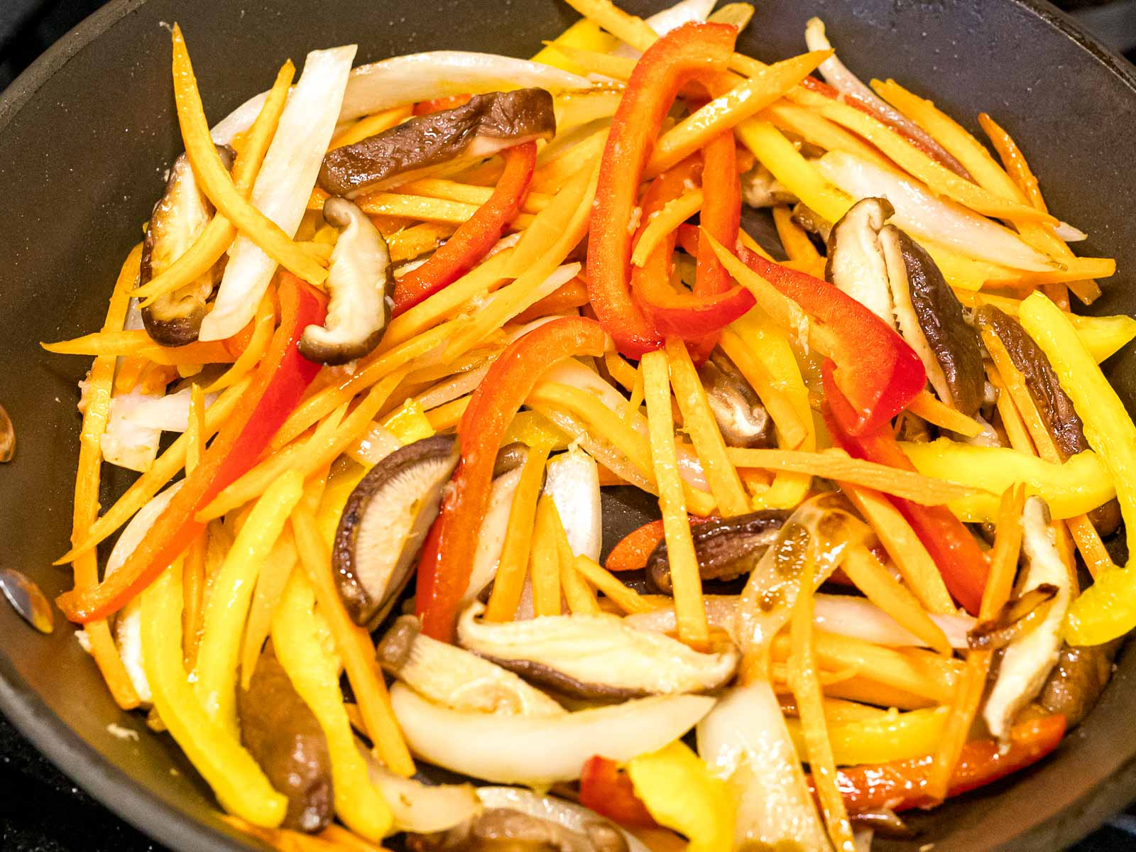 stir fried carrots, shiitake mushrooms, and bell peppers in a pan