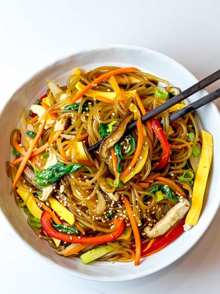japchae noodles with red peppers, carrots, and shiitake mushrooms in a white bowl with chopsticks