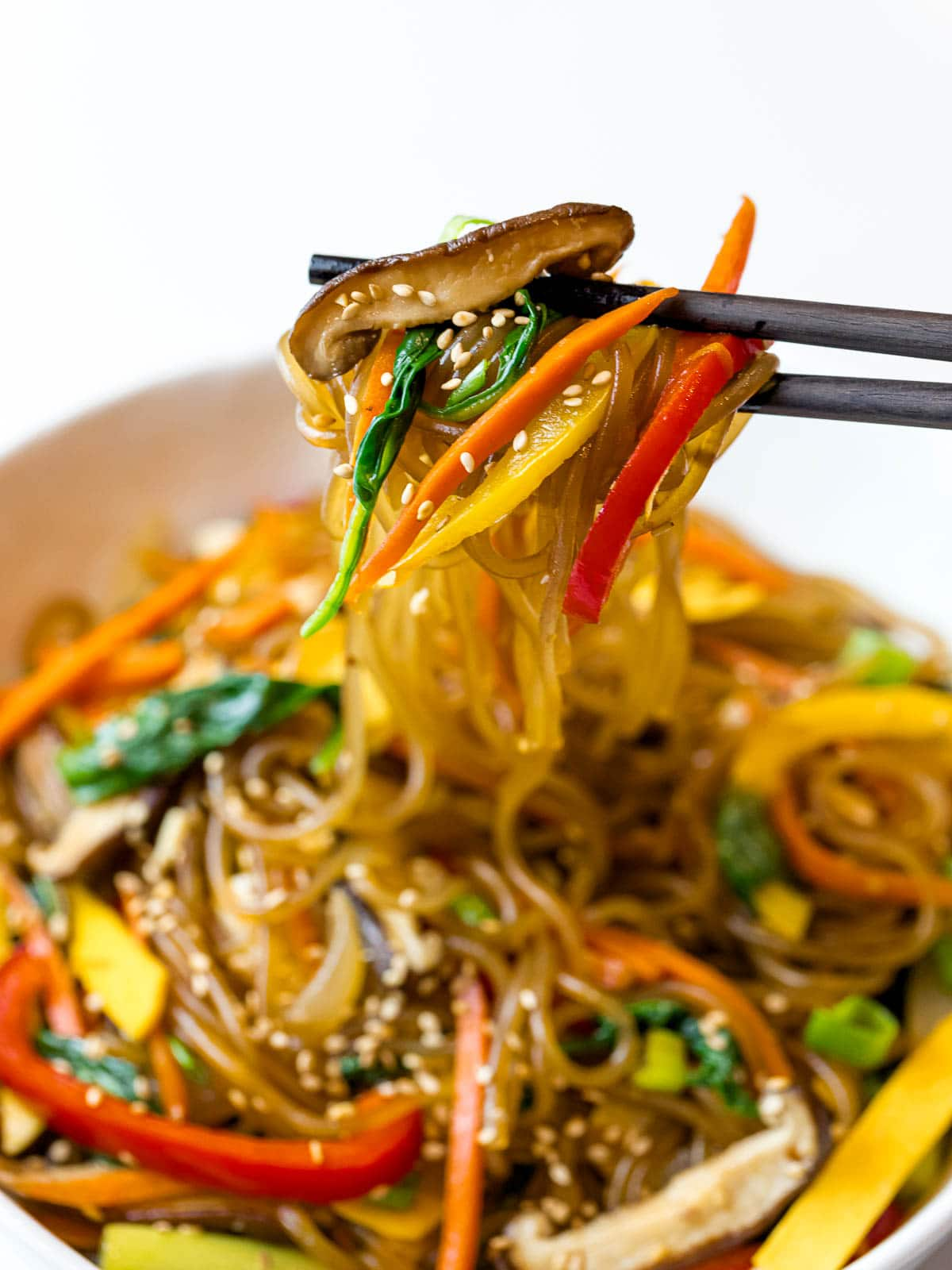 close up of Korean japchae noodles with stir fried vegetables picked up by chopsticks