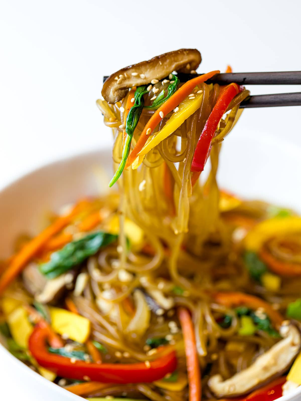 japchae glass noodles with colorful vegetables held up by chopsticks