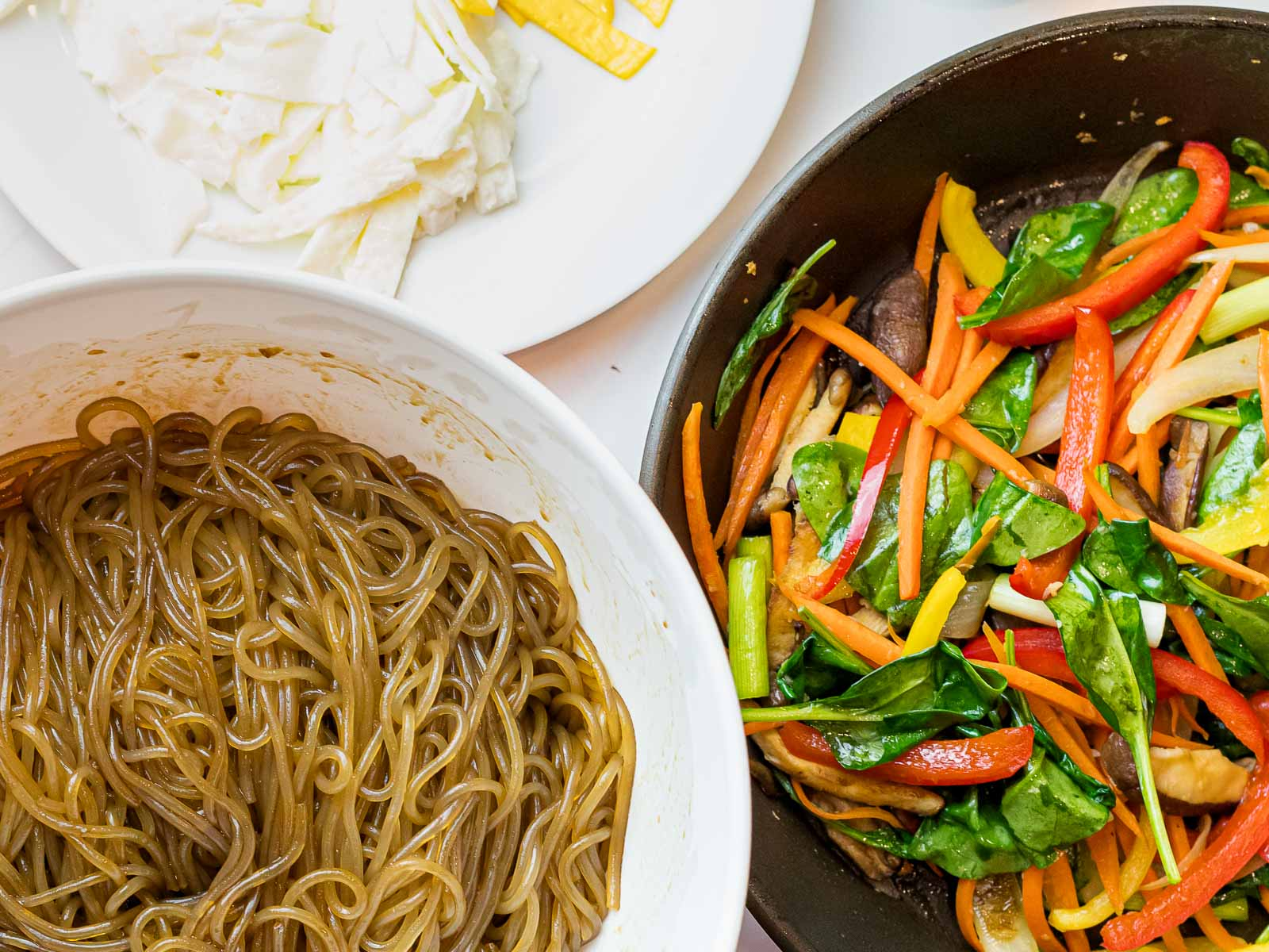 Korean glass noodles with sauce next to japchae vegetables and egg whites