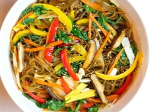 Korean japchae noodles with mushrooms, red peppers, carrots, and spinach