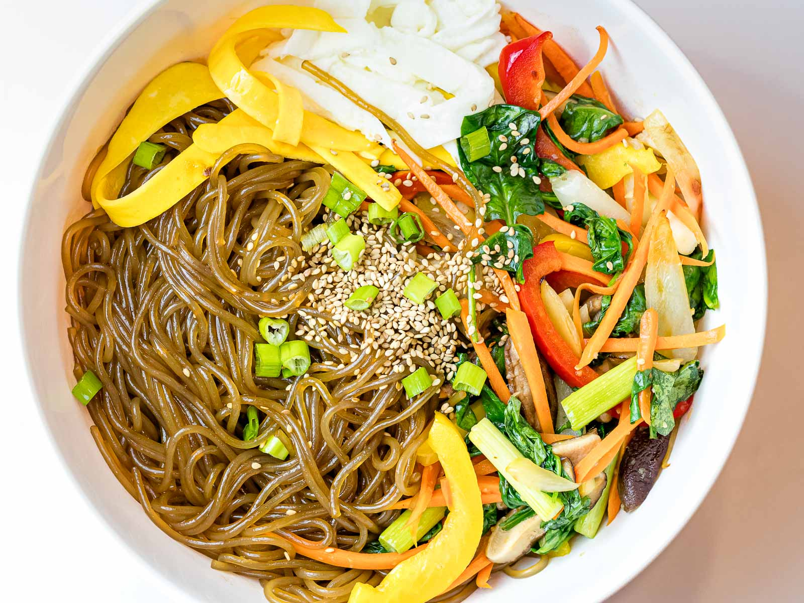 Korean glass noodles with stir fried colorful vegetables and sesame seeds