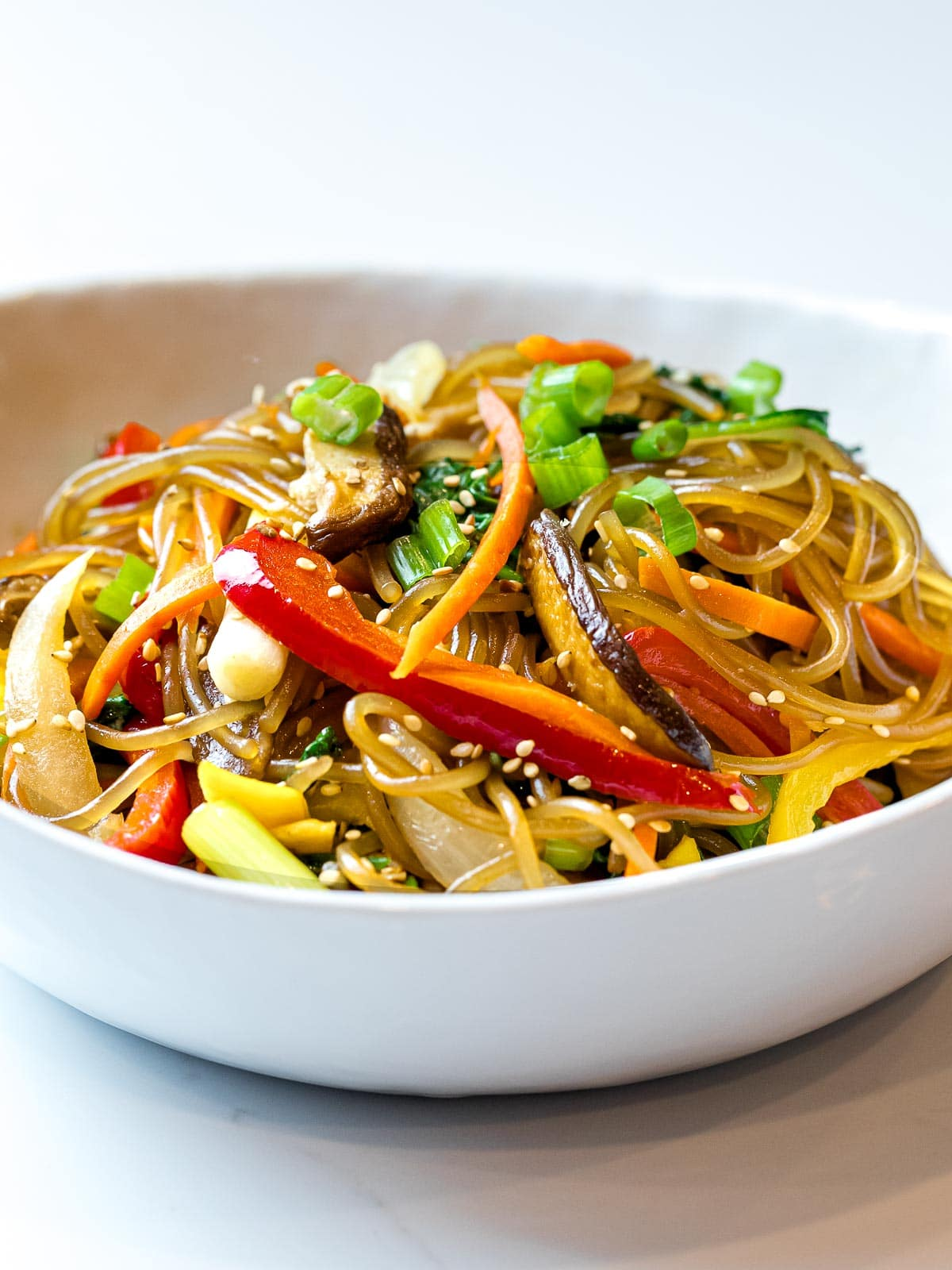 close up of Korean glass noodles, japchae, with colorful stir fried vegetables