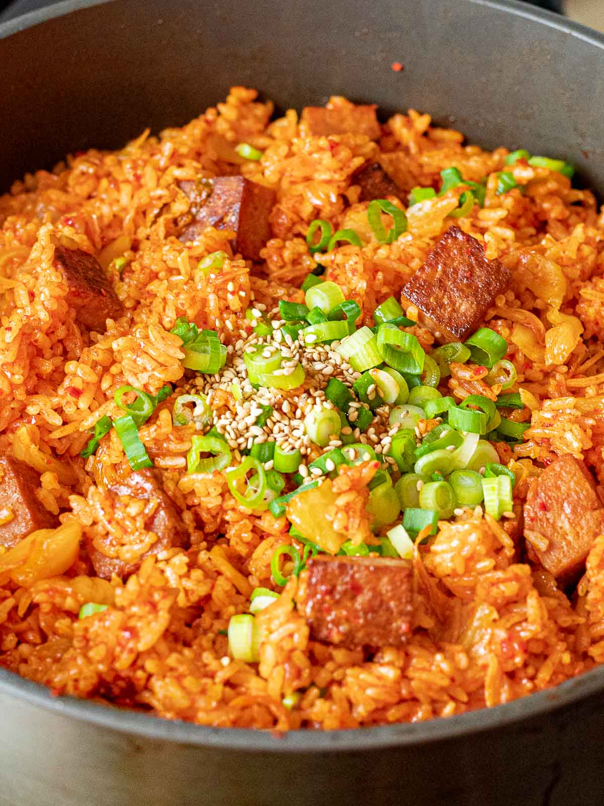 kimchi fried rice with spam with green onions and sesame seeds in a pan