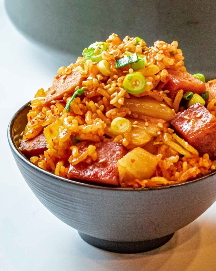 bowl of kimchi fried rice with spam topped with scallions and sesame seeds