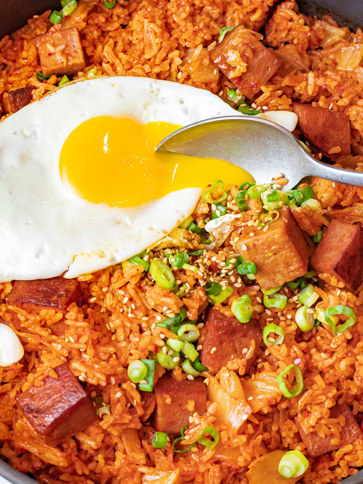 kimchi fried rice with spam topped with a sunny side up egg with a spoon