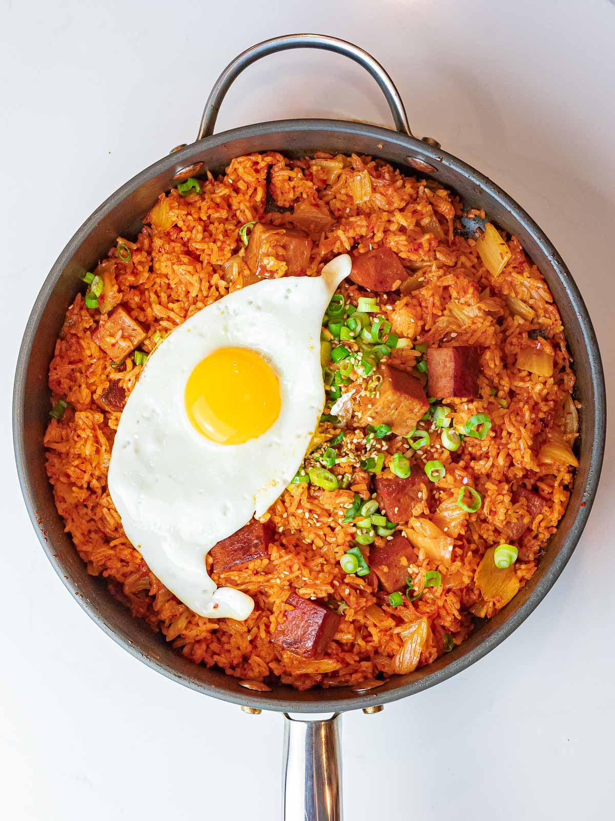 overhead of kimchi spam fried rice and a sunny side up egg with scallions