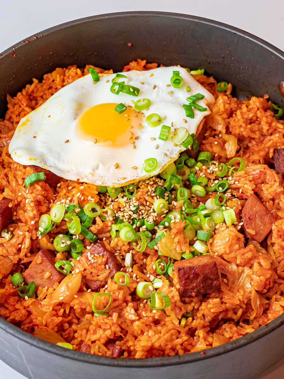 kimchi fried rice with spam and a fried sunny side up egg with scallions in a pan